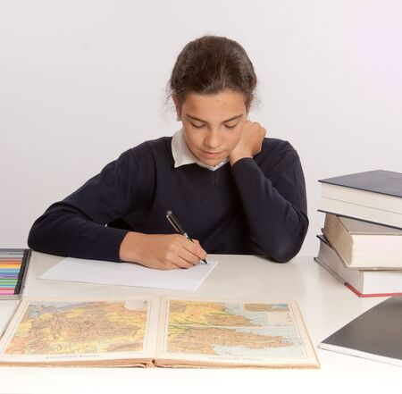 Schoolgirl writing at her desk with a concentrated expression Stock Photo - 15895798