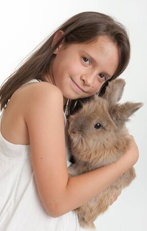 beautiful rabbit: Young girl lovingly hugging her bunny