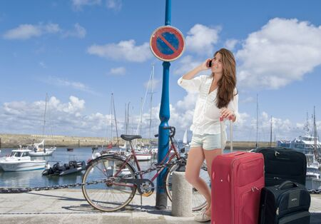 Happy Girl on the phone with her baggage by the sea shore Stock Photo - 15895802