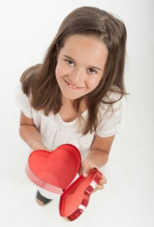 little girl surprised: Little girl holding a heart shaped gift box Stock Photo