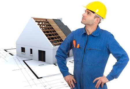 toiture maison: L'homme en salopette et casque de s�curit�, avec une maison sur la construction et les plans � l'arri�re-plan
