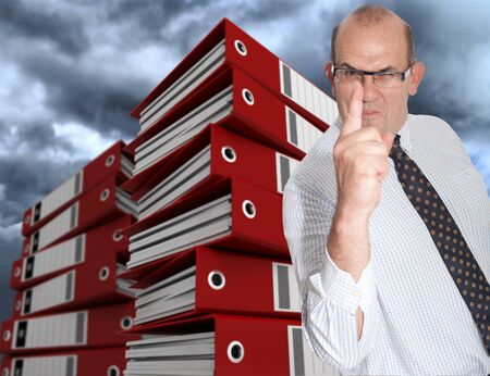 Menacing business man surrounded by piles of folders and a stormy sky photo