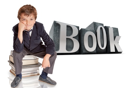 Cute young schoolboy sitting on top of a pile of books with the word book on the background  photo