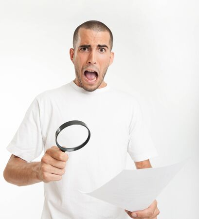 Young man reading a document through a magnifying glass with a shocked expression Stock Photo - 15895778
