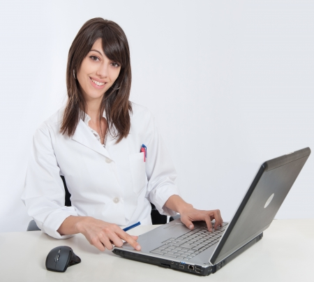 admissions:   Young female healthcare worker using her computer    Stock Photo