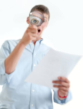 Young man with shocked expression examining a document through a magnifying lens Stock Photo - 15895782