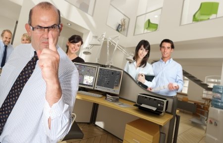 Humorous shot of a menacing business man in an office surrounded by smiling workers photo