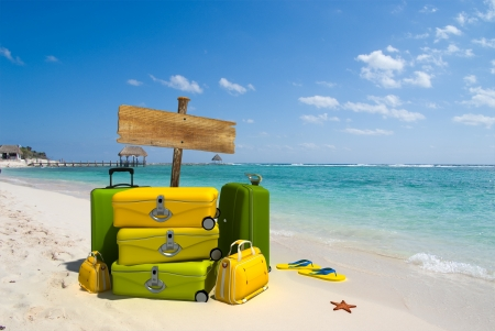 maletas de viaje: Pila de equipaje por un cartel en un resort de playa