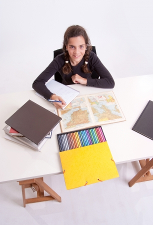 Young girl with a cheerful expression doing schoolwork  Stock Photo - 16003119