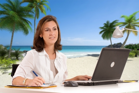 Woman at her desk with a tropical beach on the background