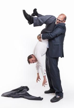 debts: Big man holding another upside down man Stock Photo