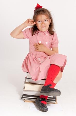 petite fille avec robe: Petite fille avec des lunettes et une expression heureuse drôle assis sur une pile de livres Banque d'images