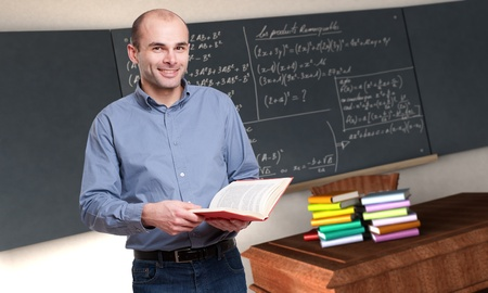 adult classroom:  Young male teacher holding a book in a maths classroom