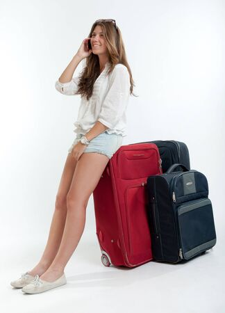 Young cute girl with luggage  talking on the phone Stock Photo - 16036533