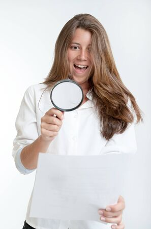 Young woman with a happy expression examining a document with a magnifying glass Stock Photo - 16036548