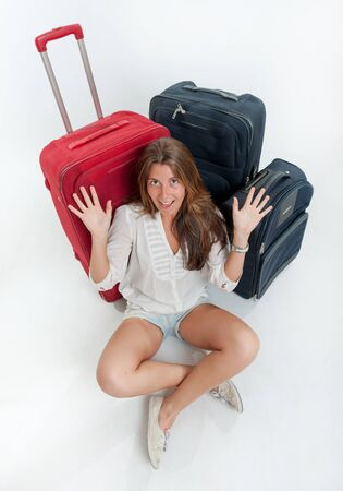 Happy young woman sitting on the floor surrounded by luggage Stock Photo - 16036557