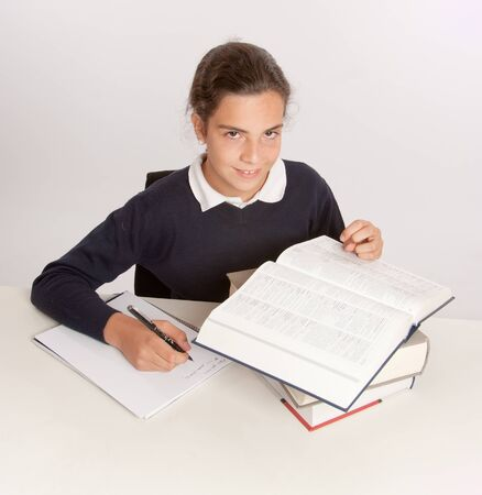 essay:  Schoolgirl consulting a dictionary while writing an essay