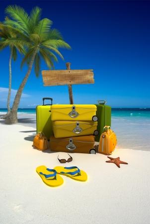 valise voyage: Pile de bagages par un panneau en bois sur une plage tropicale