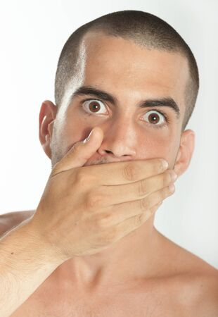 realization: Young man covering his mouth with his hand