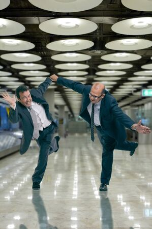 working late: Humorous shot of a pair of running businessmen at the airport