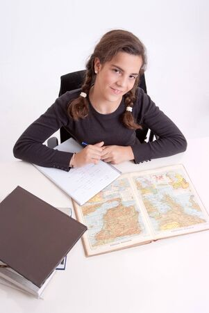 schoolwork:  Young girl with a cheerful expression doing schoolwork