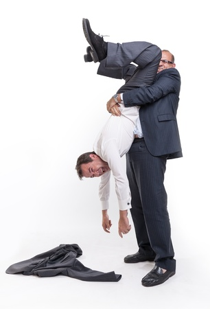 to another: Big man holding another upside down by the ankles Stock Photo