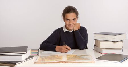 Schoolgirl writing at her desk with a happy expression Stock Photo - 16087838