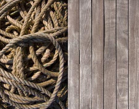 coiled rope: Contrasting textures of wooden deck and coiled rope Stock Photo