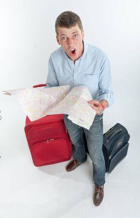 desperate: Hombre desesperado joven sosteniendo un mapa rodeado de equipaje