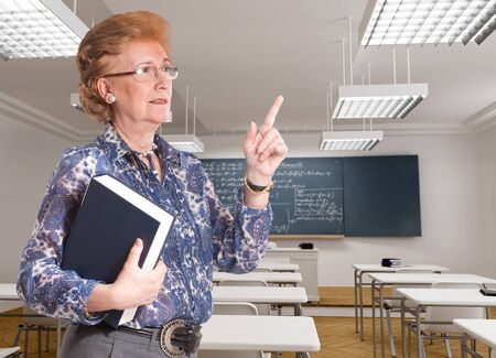 formulae:    Portrait of a smiling mature teacher in the middle of an explanation