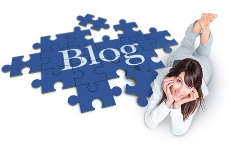 blogger: Young woman lying on the floor with a puzzle forming the word Blog Stock Photo