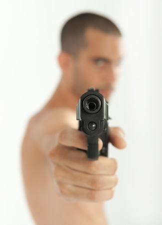 hombre disparando: El hombre apuntando con su arma a la cámara Foto de archivo