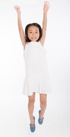 Cute little Asian girl happily jumping photo