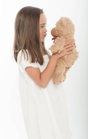 Cute little girl kissing a teddy bear