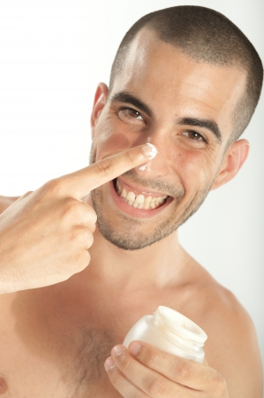 skin protection: Attractive man  applying moisturizer
