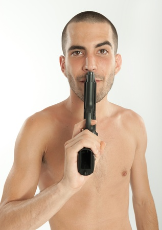 Bare-chested man holding a gun photo