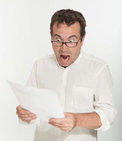 shock: Man reading a document with an scared expression