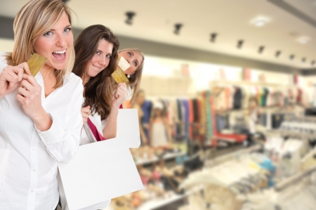 Three cute girls holding credit cards at the mall Stock Photo - 16087069