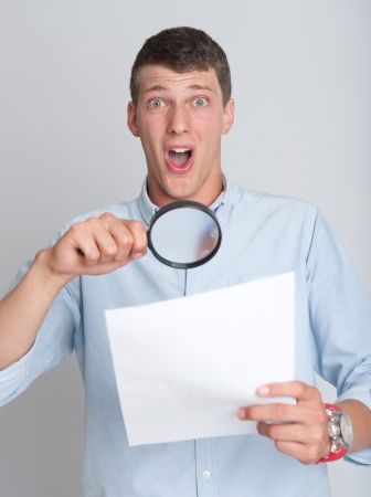 Young man with shocked expression examining a document through a magnifying lens photo