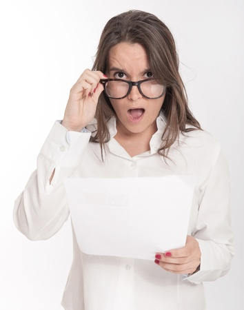dubious: Young brunette looking shocked to a document