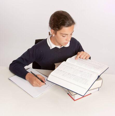 niños estudiando: Colegiala consultar un diccionario al escribir un ensayo Foto de archivo
