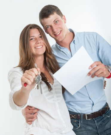 Young couple holding a document and a bunch of keys Stock Photo - 16192934