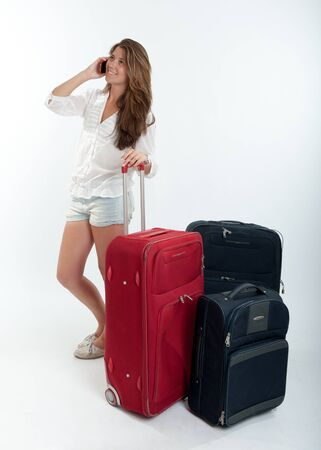 Young cute girl with luggage  talking on the phone  Stock Photo - 16192832