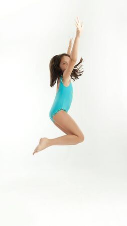 Young girl jumping in a swimsuit photo