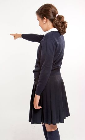 Profile view of  a schoolgirl pointing at something, isolated in white  photo