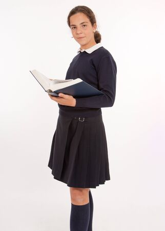 schoolgirls:  Young girl consulting a big encyclopedia  Stock Photo
