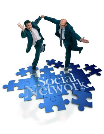 Humorous shot of a pair of running businessmen on a puzzle with the word social network Stock Photo - 16268534