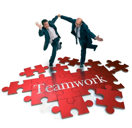 synergy: Humorous shot of a pair of running businessmen on a puzzle with the word teamwork
