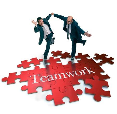 synergy: Tiro chistoso de un par de hombres de negocios que se ejecutan en un rompecabezas con la palabra trabajo en equipo Foto de archivo