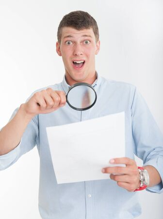 Young man with shocked expression examining a document through a magnifying lens Stock Photo - 16192916